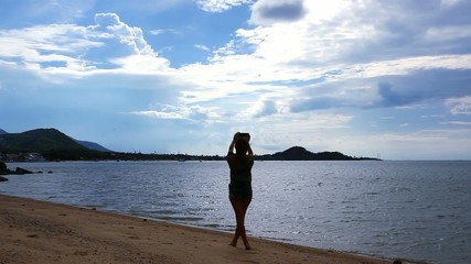 Woman taking picture of exotic beach with mobile phone on Koh