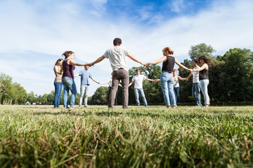 Group of friends at the park holding hands.