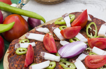 Vegetables with traditional salami on wooden plate