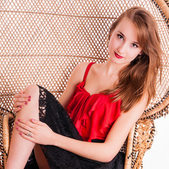 Beautiful young girl sitting in a rattan peacock chair.