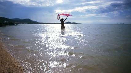 sexy woman in bikini running with pareo into sea to meet the sun