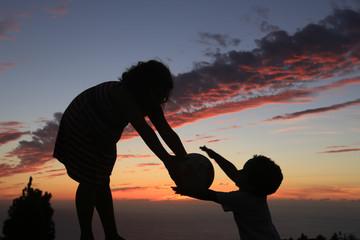 Niños jugando a la puesta del sol