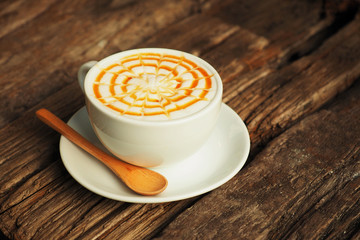 caramel coffee in white cup on wood table