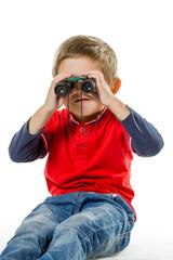 Boy sitting and looking through binoculars