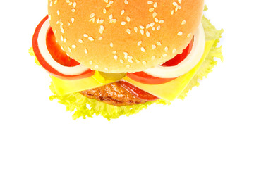 Top view of a burger with cheese, pickles, onion, tomato and sau