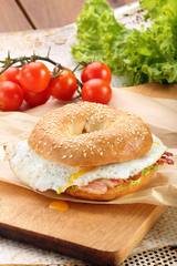 Sandwich with fried bacon and egg on a chopping board
