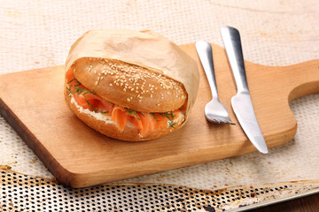 Sandwich with smoked salmon and dill wrapped in baking paper on