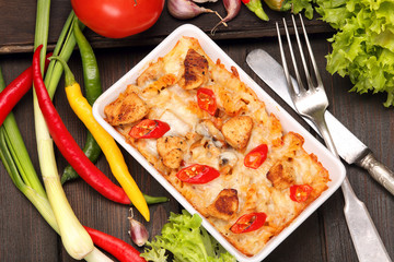 Casserole with chicken and chili peppers on a wooden background