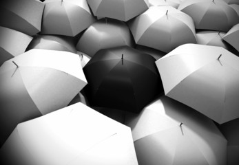Black umbrella standing out from background of white umbrellas
