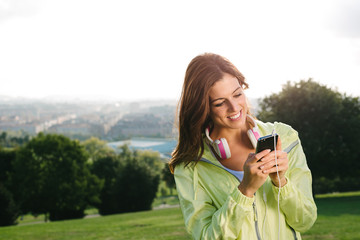 Woman with smartphone messaging during sport exercising