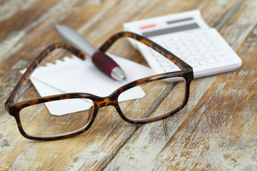 Reading glasses, calculator, pen and note paper on wood