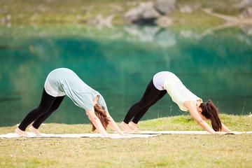 Zwei Frauen beim Yoga vor einem Bergsee in den Alpen