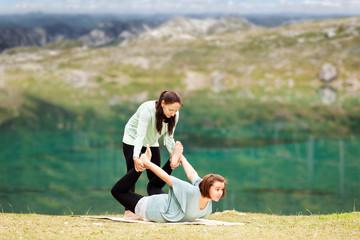 Weiblicher Yogalehrer gibt Hilfestellung beim Training