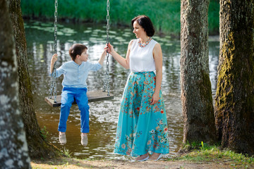 Mouther and cute little boy on swing outdoors