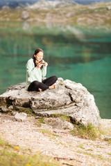 Frau sitzt auf einem Stein am Seeufer und trinkt Tee