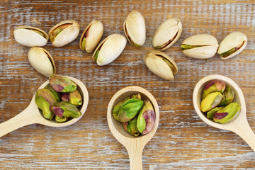 Pistachio nuts on wooden spoons on wooden surface