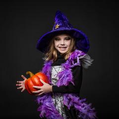 Cute little Halloween witch holding a orange pumpkin