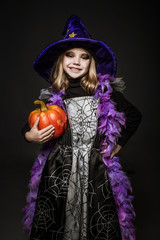Portrait of little girl in witch costume with pumpkin
