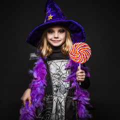 Little beautiful halloween witch with colorful candy