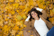 Young beautiful girl in blue jeans lying on yellow leaves