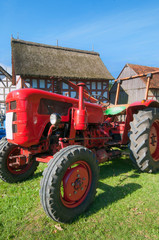 ancient tractor in front of a half timbered house