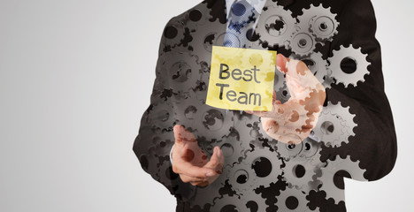 businessman hand show best team words on sticky note with abstra