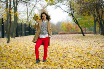 Young woman in fashion coat walking in autumn park
