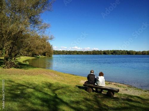canvas print picture Rentnerpaar genießt sonnigen Herbst am See