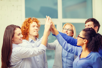 creative team doing high five gesture in office