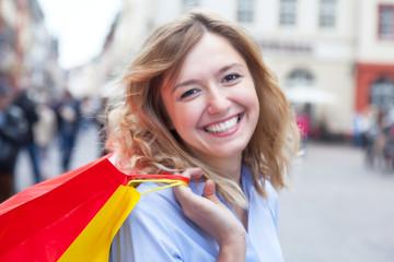 Frau mit blonden Locken hat Spass beim Einkaufen