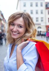 Lachende Frau mit blonden Locken beim Einkaufen