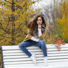 Beautiful woman sitting on a bench in autumn park