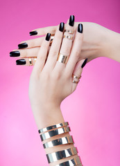 Woman with black manicure wearing gold bracelet and rings