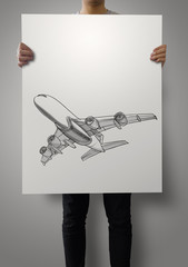 man showing hand drawn airplane on poster paper background