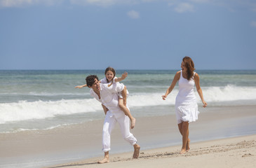 Mother, Father and Child Family Running Having Fun At Beach