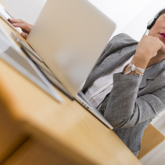 Closeup of young woman well-dressed sitting in office