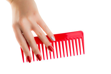 The hand of a young girl takes the red plastic brush