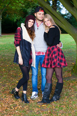 A young man with two girls in a park.