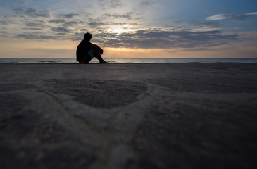 silhouetted man sitting in sunset