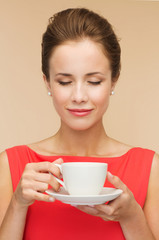 smiling woman in red dress with cup of coffee