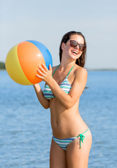 smiling teen girl in sunglasses with ball on beach
