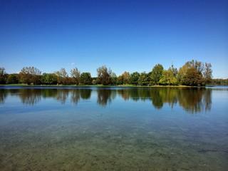 FKK-Insel im Herbst spiegelt im Feringasee
