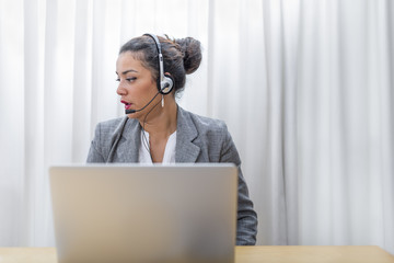 Behind her desk a saleswoman in action with headset on