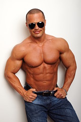 Muscular man with sunglasses poses on the wall