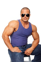 Muscular man in undershirt with sunglasses sits on chair