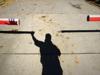 Schattenmann legt Schattenhand auf Schranke