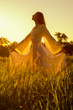 Elegant lady standing on the meadow on beautiful autumn day