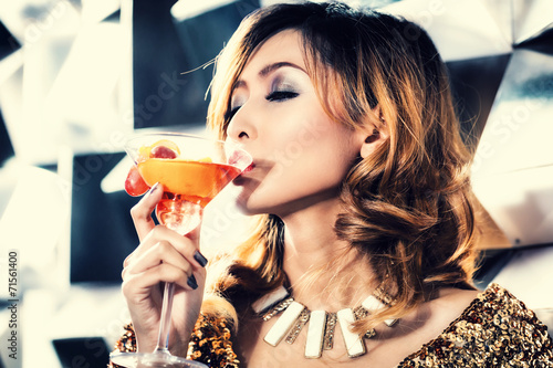 canvas print picture Asian girl drinking cocktail in fancy nightclub or bar