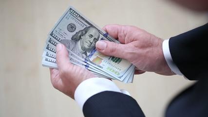 Geschäftsmann im Anzug zählt 100 Dollar Noten