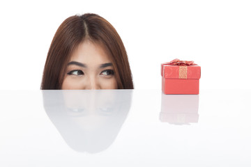 Beautiful Asian woman peeking look at red gift box